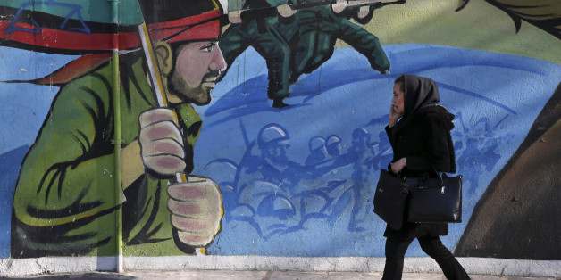An Iranian woman walks past a mural depicting Iranian armed forces in the battlefield, at Palestine Sq. in Tehran, Iran, Saturday, Jan. 16, 2016. The end of Western sanctions against Iran loomed Saturday as Iran's foreign minister suggested the U.N. atomic agency is close to certifying that his country has met all commitments under its landmark nuclear deal with six world powers. (AP Photo/Vahid Salemi)