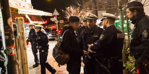 Polizisten unterhalten sich am 16.01.2016 im Nordafrikaner-Viertel von Düsseldorf (Nordrhein-Westfalen) während eine Razzia mit einem Mann. Mit mehreren Hundert Beamten ist die Polizei zu einer Razzia in das sogenannte Maghreb-Viertel eingerückt.