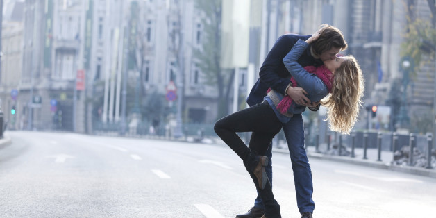 Young couple kissing in a middle of a city road.