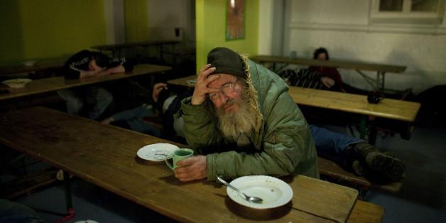 Ein obdachloser Mann sitzt in der Kältenotschlafstelle der Evangelischen Stadtmission Berlin zwischen Schlafenden. (AP Photo/Markus Schreiber)