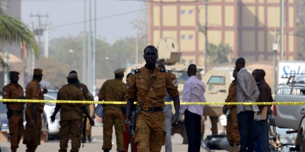 Burkina Faso's soldiers and investigators gather in front of the Splendid hotel and the cafe restaurant Capuccino on January 17, 2016 in Ouagadougou, following a jihadist attack by Al-Qaeda linked gunmen late on January 15. At least 29 people, including at least 12 foreigners, were killed in an Al-Qaeda attack on a top hotel in Burkina Faso, an unprecedented strike in the capital illustrating the expanding reach of regional jihadists. / AFP / ISSOUF SANOGO        (Photo credit should read ISSOUF