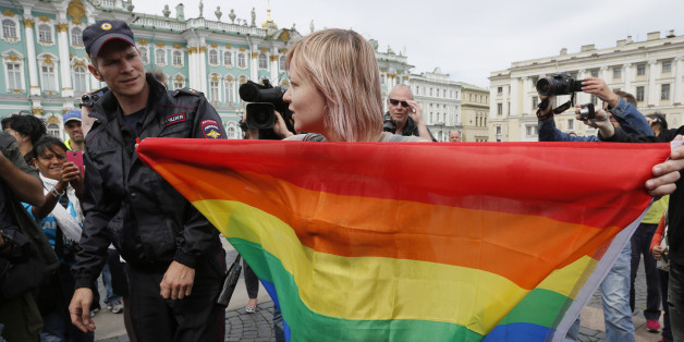A gay rights activist stands with a rainbow flag, in front of journalists, during a protesting picket at Dvortsovaya (Palace) Square in St.Petersburg, Russia, Sunday, Aug. 2, 2015. Several gay rights activists stood protesting against gay rights violation at Palace square where paratroopers celebrated Paratroopers' Day. (AP Photo/Dmitry Lovetsky)