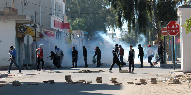"""Tunisian protesters take to the streets in the southern town of Kasserine , Tunisia, and clash with riot police during a protest against a new tax on vehicles, Wednesday, Jan. 8, 2014. Protesters called the government the """"assassin of our dreams,"""" complaining that little has changed since the country's reviled leader was ousted in 2011. (AP Photo / Mouldi Kraiem)"""