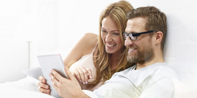 Young woman with man wearing smart glasses using digital tablet on bed