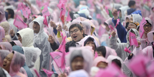 Fans of Japan's all-girl pop idol group AKB48 cheer as the group performs prior to the annual AKB48 popularity poll in Tokyo, Saturday, June 7, 2014.  In the event, fans vote their favorite group member. (AP Photo/Eugene Hoshiko)
