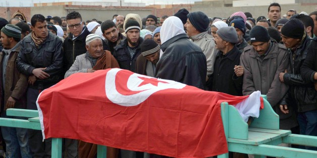 """Mourners carry the coffin wrapped by the Tunisian flag of one of the four national guards killed in an ambush during a funeral procession in Kasserine, Tunisia, Wednesday, Feb. 18, 2015. Radical militants killed four members of the National Guard in the mountainous Kasserine region near the Algerian border, Tunisia's Interior Ministry said early Wednesday. The brief statement blamed """"terrorists"""" for the attack but gave no other details. Local radio added that the attack took place around midnigh"""