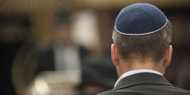 Ein Mann mit einer Kippa auf dem Kopf sitzt am 14.04.2015 im Chabad-Zentrum in Berlin beim Gedenkgottesdienst für einen getöteten 22-Jährigen aus Israel.