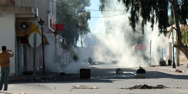 """Tunisian protesters take the streets in the southern town of Kasserine , Tunisia, and clash with riot police during a protest against a new tax on vehicles, Wednesday, Jan. 8, 2014. Protesters called the government the """"assassin of our dreams,"""" complaining that little has changed since the country's reviled leader was ousted in 2011. (AP Photo/Mouldi Kraiem)"""