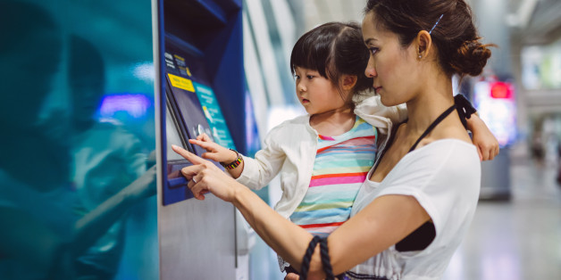 Pretty young mom carrying lovely little girl using an automatic teller machine together in the train station