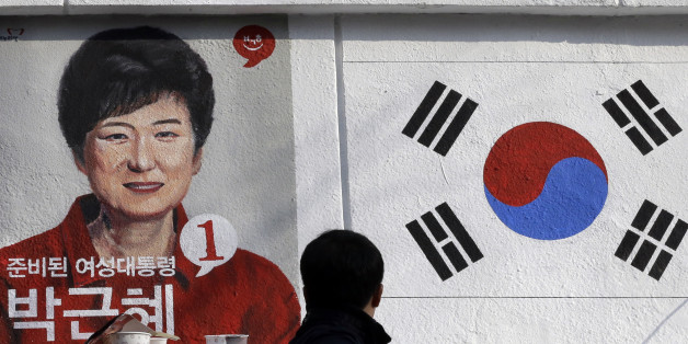A man looks at the wall paintings of South Korea's President-elect Park Geun-hye of ruling Saenuri Party and national flag at Korean Civic Education Institute for Democracy in Seoul, South Korea, Thursday, Dec. 20, 2012. The wall painting is part of renovation work for the building as well as publicizing the 18th Presidential Election which elected Park as the country's first female president. (AP Photo/Lee Jin-man)