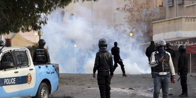 Police forces stand by tear gas during clashes in the city of Ennour, near Kasserine, Tunisia, Wednesday, Jan. 20, 2016. Tunisia has declared a curfew in the western city after clashes between police and more than 1,000 young protesters demonstrating for jobs. Tensions have risen in Kasserine since Sunday when an unemployed youth killed himself by scaling an electricity transmission tower to protest his rejection for a government job. (AP Photo/Moncef Tajouri)