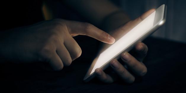 Hand touching digital tablet in darkroom
