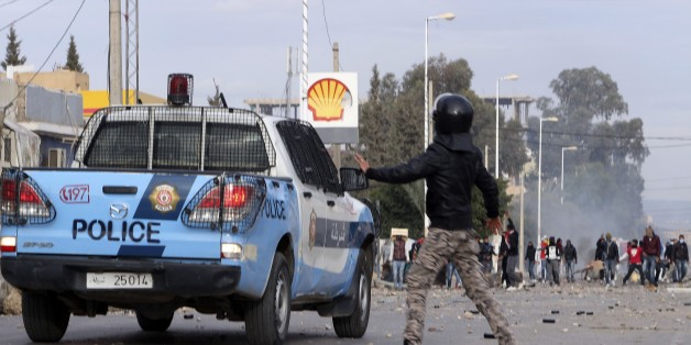 Protesters face police forces in the city of Ennour, near Kasserine, Tunisia, Wednesday, Jan. 20, 2016. Tunisia has declared a curfew in the western city after clashes between police and more than 1,000 young protesters demonstrating for jobs. Tensions have risen in Kasserine since Sunday when an unemployed youth killed himself by scaling an electricity transmission tower to protest his rejection for a government job. (AP Photo/Moncef Tajouri)