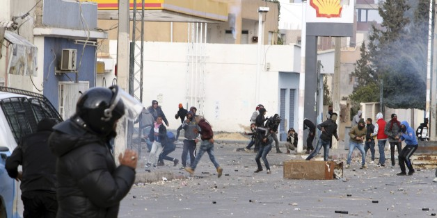 Protesters throw items to police forces in the city of Ennour, near Kasserine, Tunisia, Wednesday, Jan. 20, 2016. Tunisia has declared a curfew in the western city after clashes between police and more than 1,000 young protesters demonstrating for jobs. Tensions have risen in Kasserine since Sunday when an unemployed youth killed himself by scaling an electricity transmission tower to protest his rejection for a government job. (AP Photo/Moncef Tajouri)