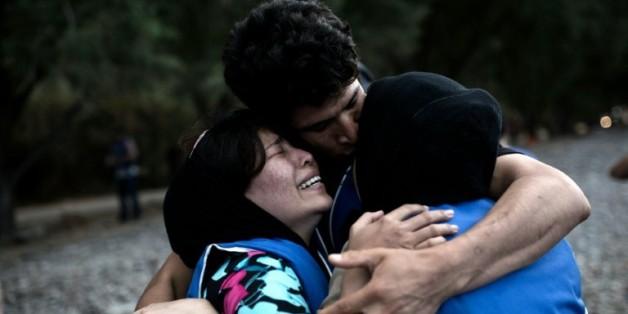 Des gens se réconfortent mutuellement à leur arrivée sur l'île grecque de Lesbos, après une traversée de la mer Egée depuis la Turquie, le 10 septembre 2015