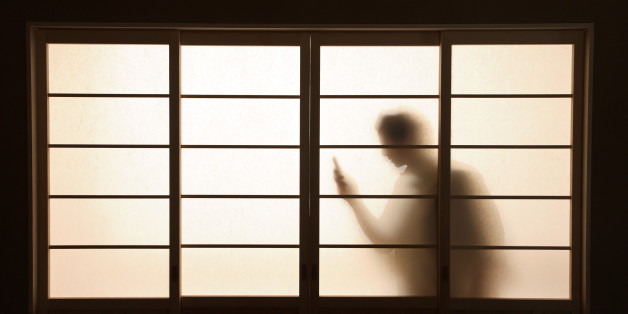 figure holding phone silhouetted behind screen