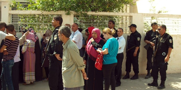 Bystanders gather in front of Tunisian Interior Minister Lotfi Ben Jeddou's residence in Kasserine, southern Tunisia, after gunmen attacked the home of the country's top security official killing four of the policeman standing guard outside, Wednesday, May 28, 2014. The attack on Interior Minister Lotfi Ben Jeddou's home in the southern city of Kasserine took place just before midnight and involved six or seven attackers. (AP Photo/Mouldi Kraiem)