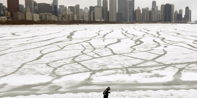 A lone jogger runs in the snow near the Adler Planetarium    and Monroe Harbor on Lake Michigan Friday, Jan. 22, 2016, in Chicago. The Chicago area will dodge a major snowstorm where one in seven Americans will get at least half a foot of snow outside their homes when this weekend's big storm has finished delivering blizzards, gale-force winds, white-out conditions and flooding to much of the eastern United States. (AP Photo/Charles Rex Arbogast)