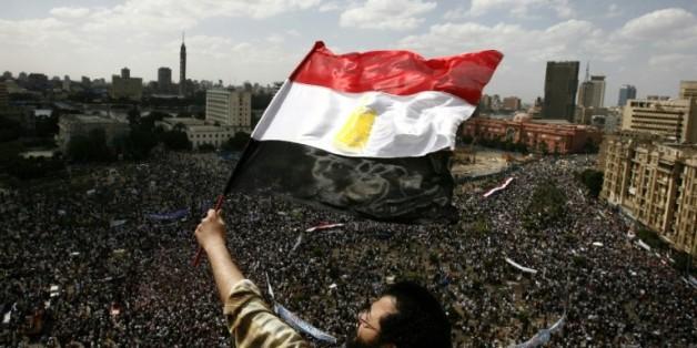 Un manifestant brandit le 8 avril 2011 un drapeau égyptien alors que des dizaines de milliers de personnes sont regroupées sur la place Tahrir, deux mois après la chute de Moubarak
