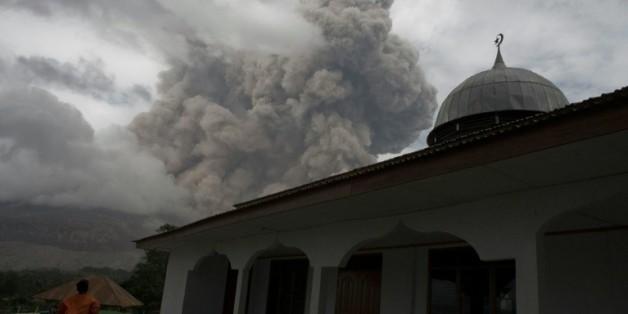 Un Indonésien se tient près d'une mosquée dans le village de Tiga Serangkai dans le nord de Sumatra, le 23 septembre 2015, pendant l'éruption du volcan Sinabung