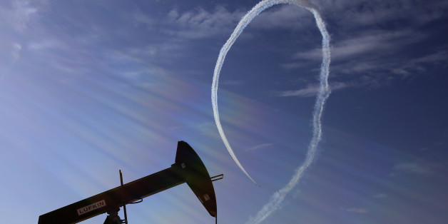 An oil pump stands as the Saudi Hawks Aerobatic Team of the Royal Saudi Air Force performs during the Bahrain International Airshow in Sakhir, Bahrain, Saturday, Jan. 23, 2016. (AP Photo/Hasan Jamali)