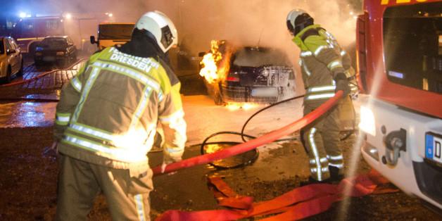 Feuerwehrleute löschen am Rande der Pegida-Demonstration am 25.01.2016 in Dresden brennende Autos.