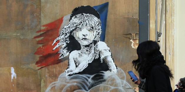 Commuters take photos on their phones of a new artwork by British artist Banksy opposite the French Embassy, in London, Monday, Jan. 25, 2016. The artwork depicts the young girl from the musical Les Miserables with tears streaming from her eyes as a can of CS gas lies beneath her. The work is criticising the use of teargas in the refugee camp in Calais. (AP Photo/Alastair Grant)