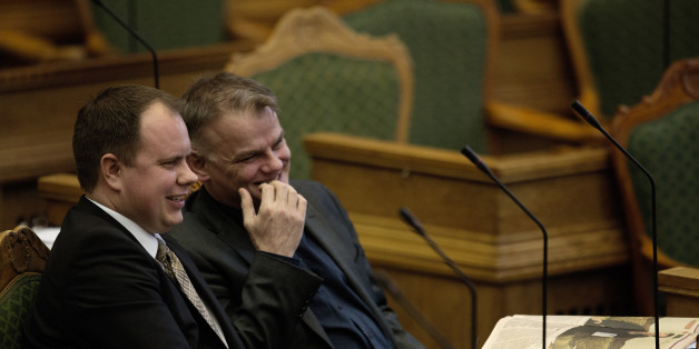 Martin Henriksen, left, and Christian Langballe from The Danish People's Party, sit in Parliament, in Copenhagen on Tuesday Jan. 26, 2016. Denmark's Parliament is expected to vote allow police seizing valuables worth more than $1,500 from asylum-seekers to help cover their housing and food costs while their cases were being processed. (Peter Hove Olesen/ POLFOTO via AP)  DENMARK OUT