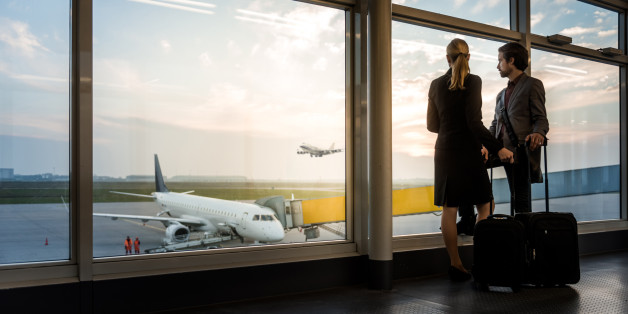 two business travellers standing at airport window and overlooking the airfield