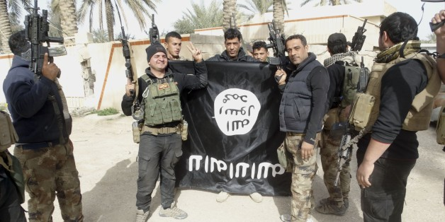 In this Tuesday, Jan. 19, 2016 photo, Iraqi security forces celebrate as they hold a flag of the Islamic State group, in Ramadi, 70 miles (115 kilometers) west of Baghdad, Iraq. The Islamic State group, which controls large parts of Syria and Iraq where it declared an Islamic caliphate in June 2014, suffered several defeats recently in both countries, including the loss of the Iraqi city of Ramadi and parts of northern and northeastern Syria over the past months. (AP Photo)