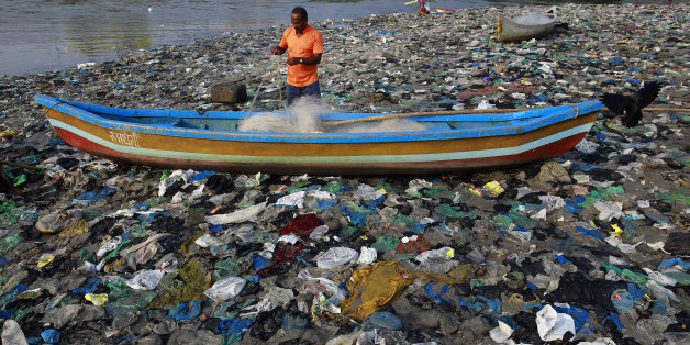 "A fisherman prepares his net on the shores of the Arabian Sea, littered with plastic bags, in Mumbai, India, Thursday, Oct. 1, 2015. Thursday marks one year since Indian Prime Minister Narendra Modi launched the ""Swachh Bharat Abhiyaan"" or ""Clean India Mission."" (AP Photo/Rafiq Maqbool)"