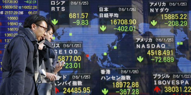 People walk past an electronic stock indicator of a securities firm showing global stock shares including Japan's Nikkei 225, top center, that lost 2.4 percent to 16,708.90, in Tokyo, Tuesday, Jan. 26, 2016. Asian stock markets sank Tuesday, led by a plunge in the Shanghai index, after a renewed slump in the price of oil kept investors on edge about the global economy. (AP Photo/Shizuo Kambayashi)