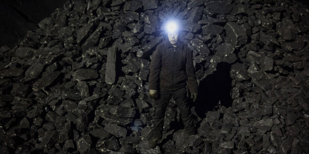 SHANXI, CHINA -NOVEMBER 25: (CHINA, HONG KONG, MACAU, TAIWAN OUT) A Chinese mine worker wears a headlamp as he stands in a pile of coal at a mine on November 25, 2015 in Shanxi, China. A history of heavy dependence on burning coal for energy has made China the source of nearly a third of the world's total carbon dioxide (CO2) emissions, the toxic pollutants widely cited by scientists and environmentalists as the primary cause of global warming. China's government has publicly set 2030 as a deadl