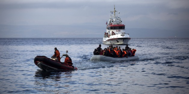 Officers of the European Union border security agency, Frontex, pull a dinghy with migrants to Skala Sikaminias village on the northeastern Greek island of Lesbos, Wednesday, Oct. 21, 2015. Greece is the main entry point for those fleeing violence at home and seeking a better life in the European Union. More than 500,000 people have arrived so far this year on Greece's eastern islands, paying smugglers to ferry them across from nearby Turkey. (AP Photo/Santi Palacios)
