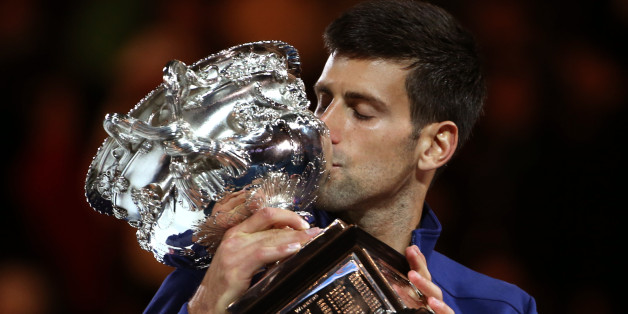 Novak Djokovic of Serbia kisses his trophy after defeating Andy Murray of Britain in the men's singles final at the Australian Open tennis championships in Melbourne, Australia, Sunday, Jan. 31, 2016.(AP Photo/Rick Rycroft)