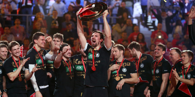 KRAKOW, POLAND - JANUARY 31: Fabian Wiede of Germany holds the trophy while his teammates celebrate the victory during the trophy ceremony following the final of the Men's EHF European Handball Championship 2016 between Spain and Germany at Tauron Arena on January 31, 2016 in Krakow, Poland. (Photo by Jean Catuffe/Getty Images)