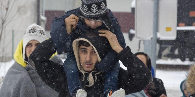 A group of migrants move through snow towards a train station to be transferred to Austria, near the border with Croatia, in Dobova, Slovenia, Sunday, Jan. 3, 2016. (AP Photo/Darko Bandic)