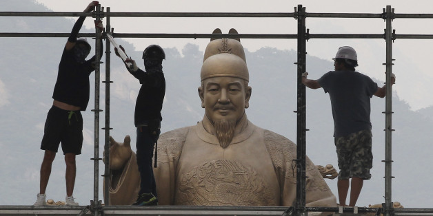 Construction workers set up a stage in front of a statue of Chosun Dynasty's King Sejong for public viewing for the 2014 Brazil World Cup, in Seoul, South Korea, Tuesday, June 17, 2014. South Korea will play Russia, Belgium and Algeria in the World Cup soccer tournament. (AP Photo/Ahn Young-joon)
