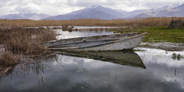 Old and semi sunken wooden boat in Prespa lake, Florina, Greece, in autumn