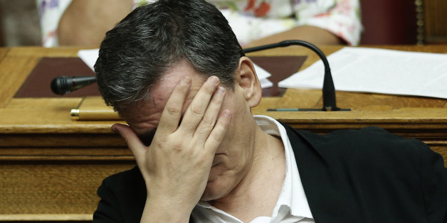 Greek Finance Minister Euclid Tsakalotos covers his face during a parliamentary session in Athens, early Friday, Aug. 14, 2015. The Greek government defended its new bailout program in tumultuous parliamentary sessions as it faced a rebellion in the governing Syriza party ahead of a vote on the deal. (AP Photo/Yannis Liakos)