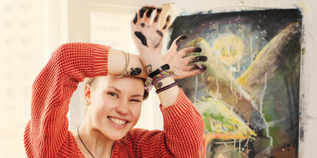 Portrait of beautiful woman artist with quirky expressions and touching her face in home art studio