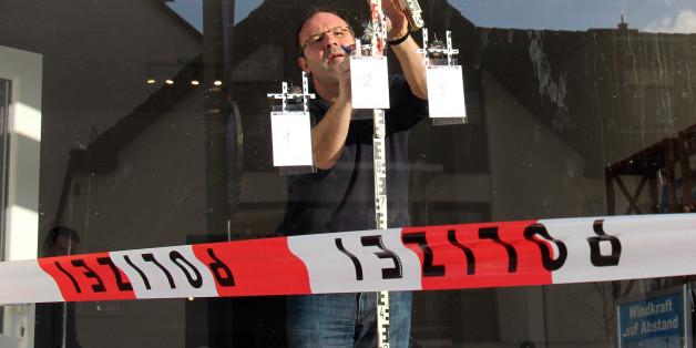Ein Beamter der Spurensicherung vermisst am 03.02.2016 in Arnsberg (Nordrhein-Westfalen) die Einschusslöcher in der Scheibe des AfD-Büros. In Arnsberg haben Unbekannte auf ein Büro der Ratsfraktion der rechtspopulistischen Partei Alternative für Deutschland (AfD) geschossen.