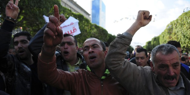 Unemployed tunisian people stage a protest in a precarious calm enforced by a nationwide curfew in Habib Bourguiba avenue, center downtown of Tunis, Saturday Jan. 23, 2016.  Tunisia's president vowed Friday to end the cycle of unrest that has pummeled towns across the country as authorities imposed a nationwide curfew, five years after the nation, convulsed by protests, overthrew its longtime ruler and moved onto the road to democracy. (AP Photo/Riadh Dridi)