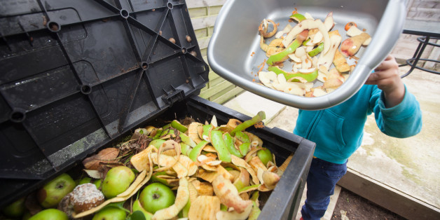 A young boy tips a bowl of apple peels into a compost bin