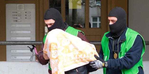 Polizisten führen einen mit einem Tuch verdeckten Verdächtigen ab