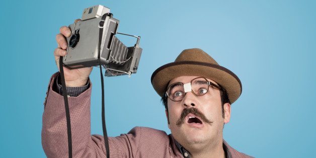 Portrait of nerd photographer taking a selfie with an old fashioned camera over blue background.