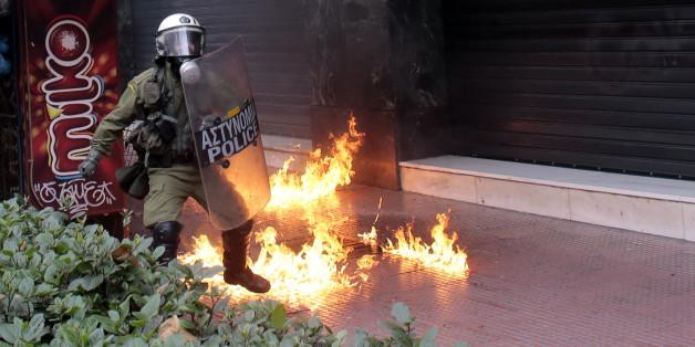 Ein Polizist im Feuer bei Ausschreitungen Anfang Februar in Athen.