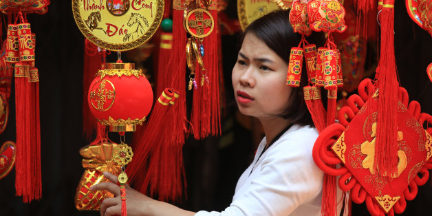 A woman looks at Lunar New Year decorations in the old quarter of Hanoi, Vietnam on Saturday, Feb. 6, 2016. Vietnam will celebrate Lunar New Year, known locally as Tet, on Monday, Feb. 8. (AP Photo/Hau Dinh)