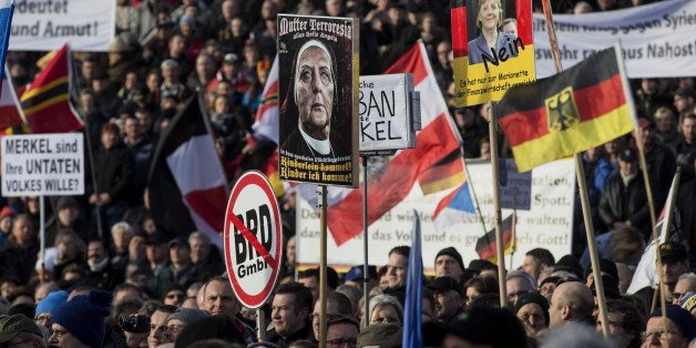 DRESDEN, GERMANY - FEBRUARY 6: Supporters of Pegida (Patriotic Europeans against the Islamization of the West) hold banners during a demonstration called 'Patriotic's day' at Konigsufer square in Dresden, Germany on February 6, 2016.  (Photo by Mehmet Kaman/Anadolu Agency/Getty Images)