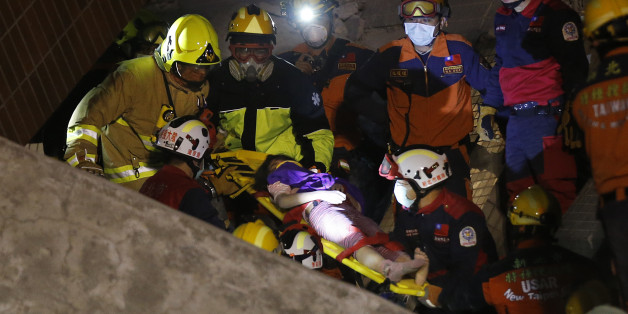 A female is rescued from a collapsed building complex after  an early morning earthquake in Tainan, Taiwan, Saturday, Feb. 6, 2016. A 6.4-magnitude earthquake struck southern Taiwan early Saturday, toppling at least one high-rise residential building and trapping people inside. (AP Photo/Wally Santana)